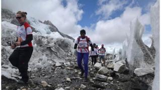 Runners, clad in warm clothing and hiking boots, run over rocky terrain, surrounded by ice, as they compete in the world's highest marathon, on 29 May. Photo released by organisers Himex.