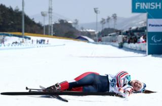 Vilde Nilsen of Norway lies on the ground whilst smiling after crossing the finishing line