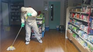 A man in protective clothing cleaning the County Oak Medical Centre