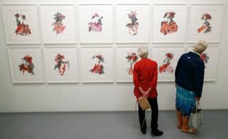 Two women look at artworks by Nigerian artist Taiye Idahor on exhibit at the Zeitz Museum of Contemporary Art Africa (Zeitz MOCAA) at the V&A Waterfront in Cape Town, South Africa 15 November 2017