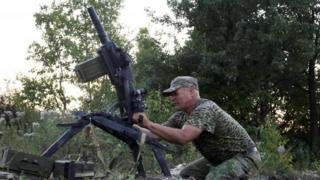 A Ukrainian government soldier fires a grenade launcher in the Donetsk region. Photo: August 2015