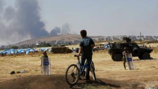 A boy on a bike watches smoke over the Syrian town of Kobane from Turkish territory, 27 June