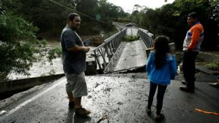 People look at a bridge destroyed by Hurricane Otto in Guayabo de Bagaces, Costa Rica