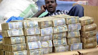 رجل يتحدث عبر الهاتف المحمول وأمامه أكوام ضخمة من الأوراق النقدية