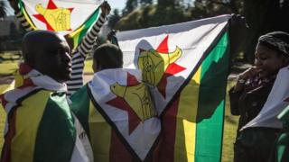 A Zimbabwean 'myflag' activist draped in their national flag gather in Pretoria on 14 July 2016 prior to a march to the Zimbabwean embassy.