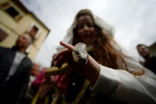 A faithful in traditional clothing carries a snake to place on the statue of Saint Domenico during an annual procession in the streets of Cocullo
