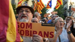 "A man holds a placard reading ""Som Sobirans"" (We are sovereign) during a demonstration calling for Spain's interior minister to resign."