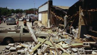 Debris covers a nearby sidewalk in the aftermath of the Oklahoma city bombing.