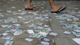 Eleitor anda sob centenas de santinhos