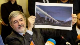Mayor of Genoa Marco Bucci displays a section plan of the new bridge.