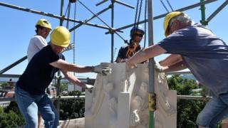 Stonemason lifting a pinnacle