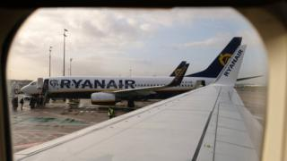 A view of one Ryanair passenger plane on the tarmac, seen through the window of another aircraft looking down the wing