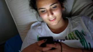 فتاة تتصفح هاتفها المحمول