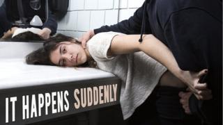 Mujer en un baño, con un hombre forzándola a agacharse
