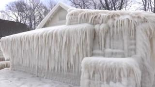 A house is seen completely encased in ice - but still recognisable as a shape - encased in icicles