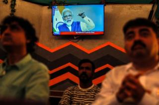 People watch a live address by Indian Prime Minister Narendra Modi after the government scrap Article 370, at a restaurant in Mumbai, India, 08 August 2019.