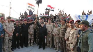 イラク軍と共に勝利を祝うアバディ首相(写真中央)