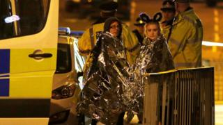 Two women wrapped in thermal blankets stand near the Manchester Arena, where US singer Ariana Grande had been performing