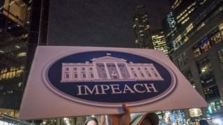 Sign reads 'IMPEACH' at the RISE and RESIST protest held at the TRUMP INTERNATIONAL TOWER on December 21, 2017 in New York City