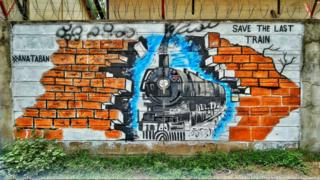 A picture of a train approaching a brick wall is painted on a wall