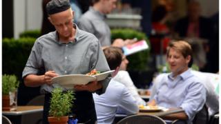 Waiter clearing an outdoor table at a restaurant