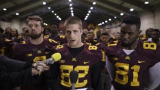 University of Minnesota wide receiver Drew Wolitarsky (centre), reads a statement on behalf of the players in the Nagurski Football Complex in Minneapolis, Minnesota, 15 December 2016
