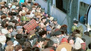 Толпа людей с чемоданами и сумками у парома в бакинской бухте