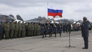 Guards walk past a line-up of troops during a welcome ceremony for Russian military personnel who returned from Syria at an airbase near the Russian city Voronezh (15 March 2016)
