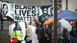 Demonstrators in front of a Black Lives Matter banner