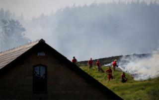 Fire fighters tackle a moorland fire near a building at Winter Hill, near Rivington, on 1 July 2018.