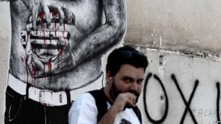 A man in Athens passes by a graffiti showing a euro sign bleeding