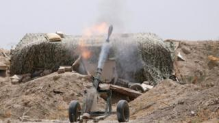 Fighters of the Syria Democratic Forces fire a mortar shell towards positions held by Islamic State fighters in northern province of Raqqa, 27 May 2016.