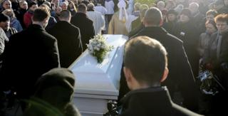 People gather in front of the church after a funeral Mass for the Polish truck driver Lukasz Urban, who was killed in the Berlin Christmas market attack, in the church in Banie, Poland, 30 December