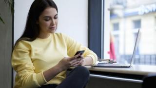 سيدة تستخدم هاتفها المحمول
