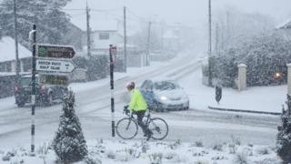 A person cycles in snowy conditions in Rathcoole in Dublin.