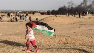 طفل فلسطينية ترفع العلم الفلسطيني قرب الحدود بين إسرائيل وقطاع غزة