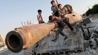 Children in Syria playing by a destroyed tank