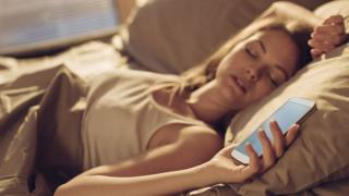 woman asleep holding mobile phone