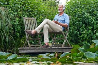 رجل يجلس في حديقة المنزل ويسمع الموسيقى