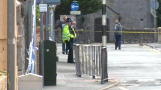 A police officer staffs a cordon at the scene