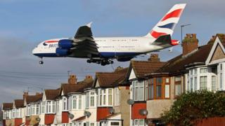 A plane over rooftops next to Heathrow airport