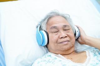 Woman in hospital bed wearing headphones