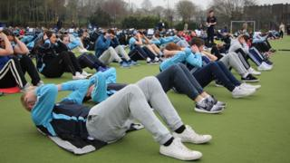 Staff and pupils doing sit-up exercises during the world record attempt