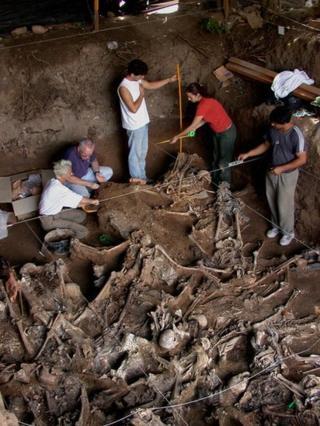 Hombres y mujeres excavando en un lugar lleno de esqueletos que están medio sepultados.