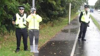 Police officers standing beside cutout officer