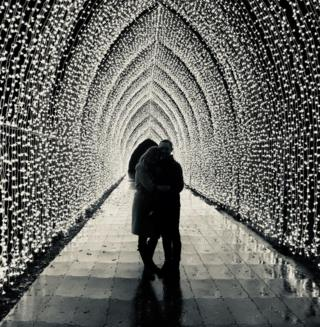 Two people standing in a tunnel of lights