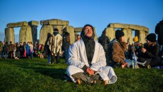 Чоловік у позі йоги біля Стоунхенджу