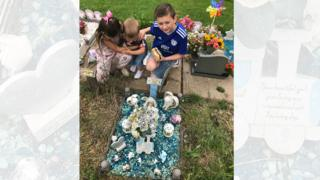 Laura Williams's children Morgan, 10, Keeley, eight, and Rueben, two, at Leo's grave