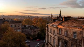 A view of Glasgow over rooftops at sunrise.
