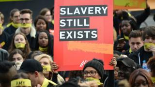protest sign reading slavery still exists